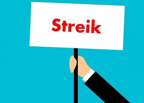 Illustrasjon av ei hand som held ein plakat med streik på